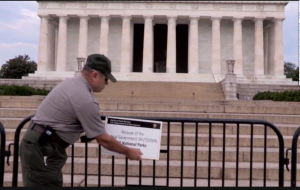 "a National Park Service guard puts up a closed sign in front of the Lincoln Memorial, reading ""because of the federal government shutdown all national parks are closed."""