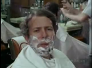 Dr. Milgram, a middle-aged white professor with poofy hair, demonstrating social contexts, with shaving cream on his face