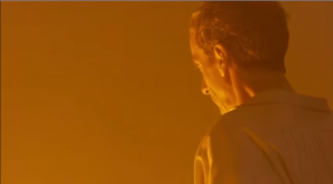 The Doctor looking down into the Thames, everything orange...